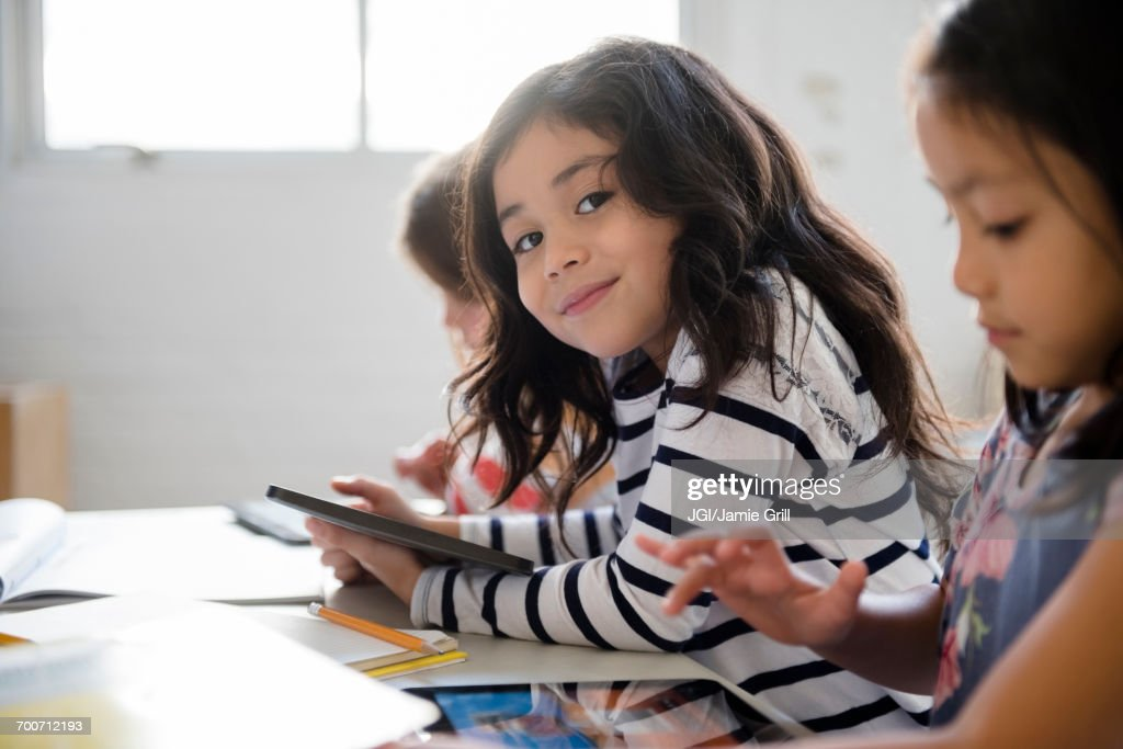 Portrait of smiling girl using digital tablet in classroom : Stock Photo