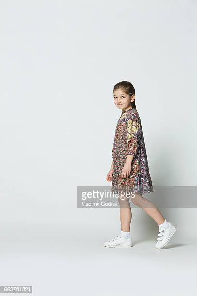 portrait of smiling girl walking against white background - 横からの視点 ストックフォトと画像