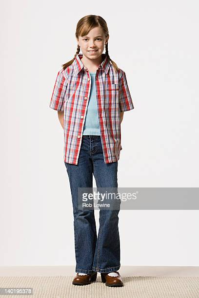Portrait of smiling girl (8-9) wearing checked shirt, studio shot