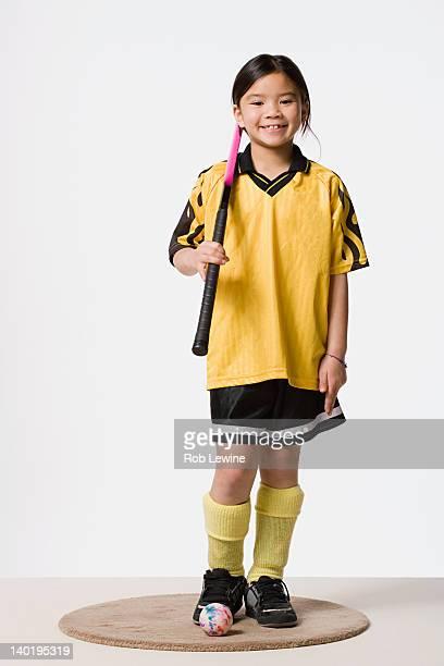 Portrait of smiling girl (8-9) wearing field hockey costume, studio shot