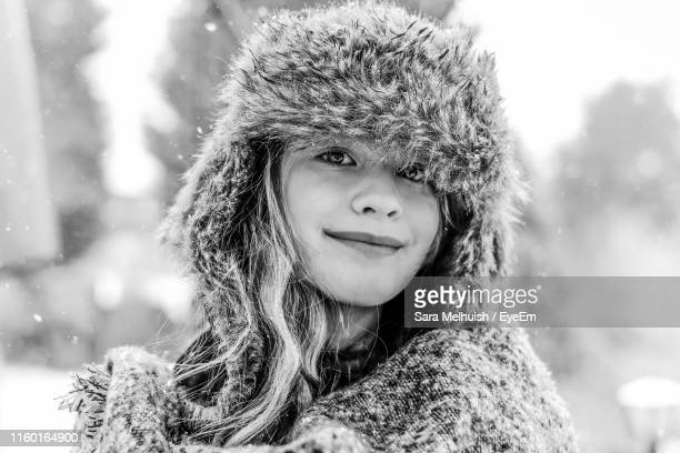 portrait of smiling girl wearing fur hat during winter - fur hat stock pictures, royalty-free photos & images