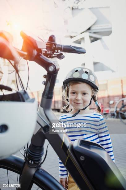 Portrait of smiling girl wearing helmet next to bicycle