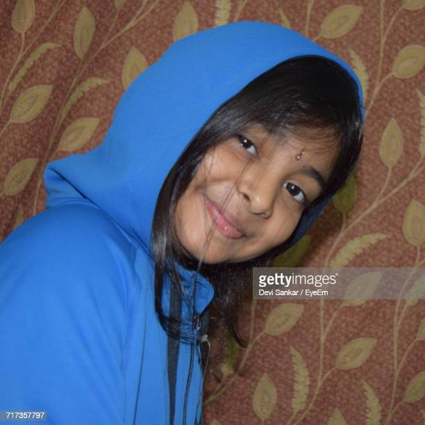 Portrait Of Smiling Girl Wearing Hood Against Curtain