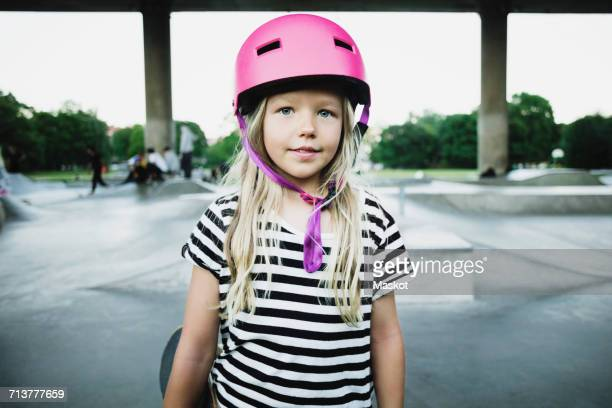 portrait of smiling girl wearing pink helmet standing at skateboard park - sports helmet stock pictures, royalty-free photos & images