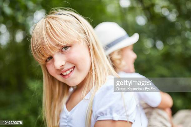 Portrait Of Smiling Girl With Blond Hair Outdoors