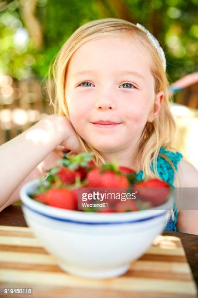 Portrait of smiling girl with bowl of stawberries