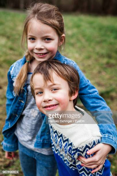portrait of smiling girl with brother standing on field - sister stock photos and pictures