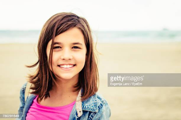 Portrait Of Smiling Girl With Brown Hair At Beach