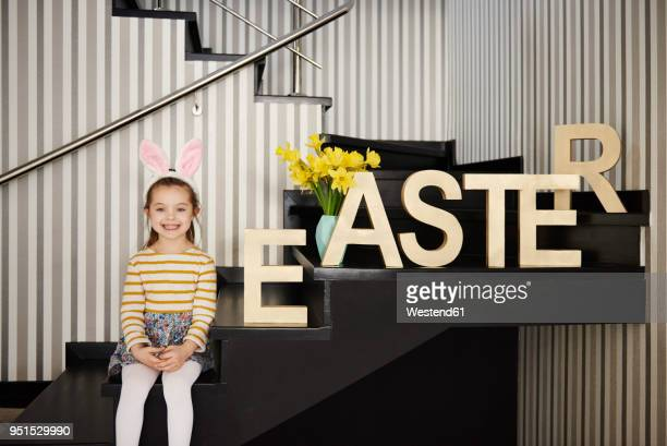 portrait of smiling girl with bunny ears sitting on stairs next to word 'easter' - happy easter text stock pictures, royalty-free photos & images