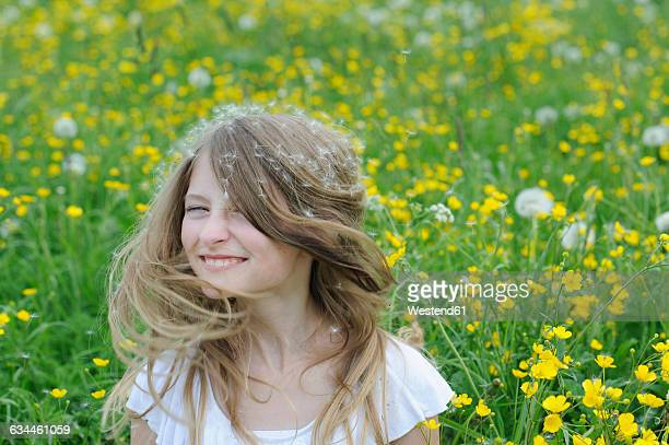 Portrait of smiling girl with dandelion seed on her hair