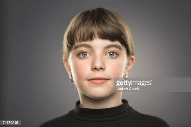 portrait of smiling girl with gray eyes against gray background - 10 11 ans photos et images de collection