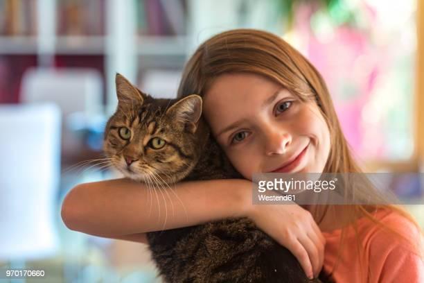 portrait of smiling girl with her tabby cat - un animal fotografías e imágenes de stock