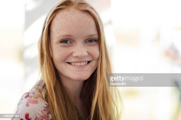 Portrait of smiling girl with long red hair
