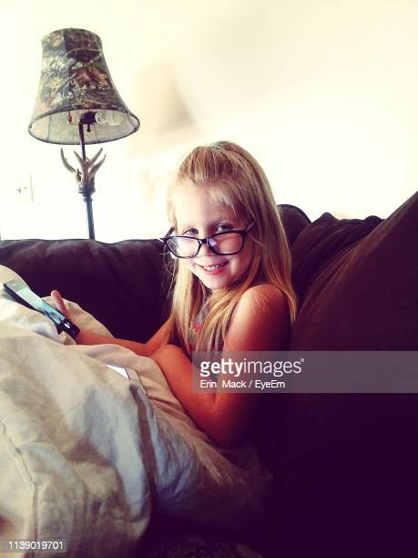 portrait of smiling girl with phone sitting on sofa at home - mack stock pictures, royalty-free photos & images