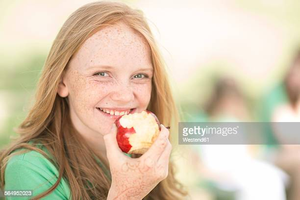 Portrait of smiling girl with red hair eating an apple