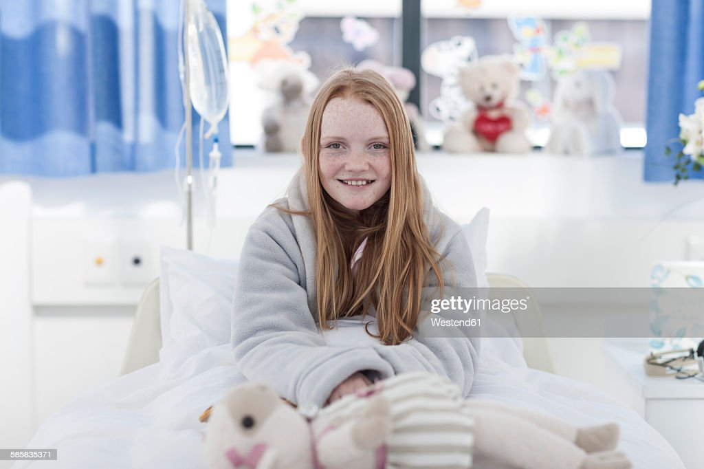 Portrait Of Smiling Girl With Red Hair In Hospital Bed