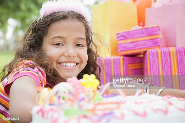 Portrait of smiling girl (10-12) with stack of gifts