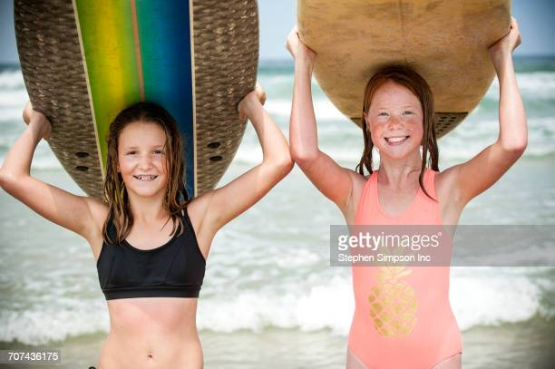 Portrait of smiling girls balancing surfboards on top of heads