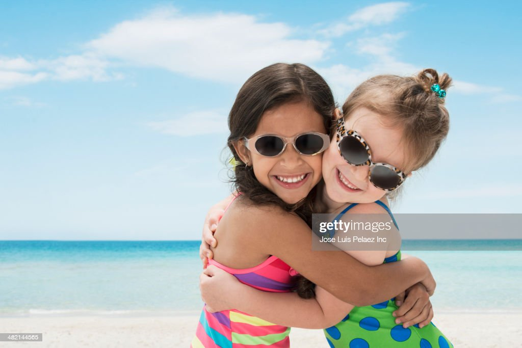 Portrait of smiling girls hugging on beach : Stock Photo