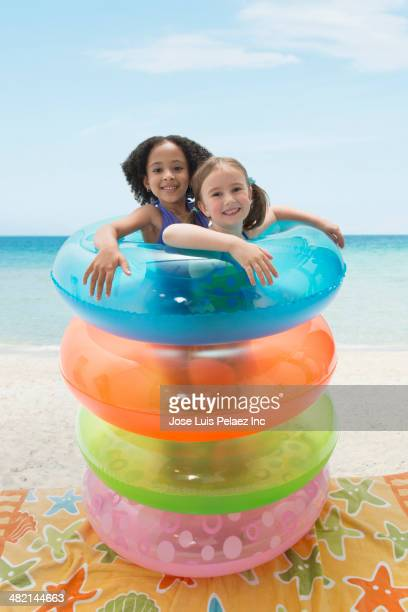 Portrait of smiling girls playing in inflatable rings on beach