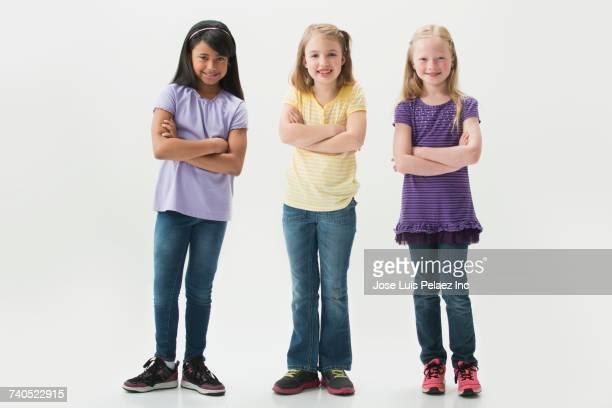portrait of smiling girls with arms crossed - 8 9 años fotografías e imágenes de stock