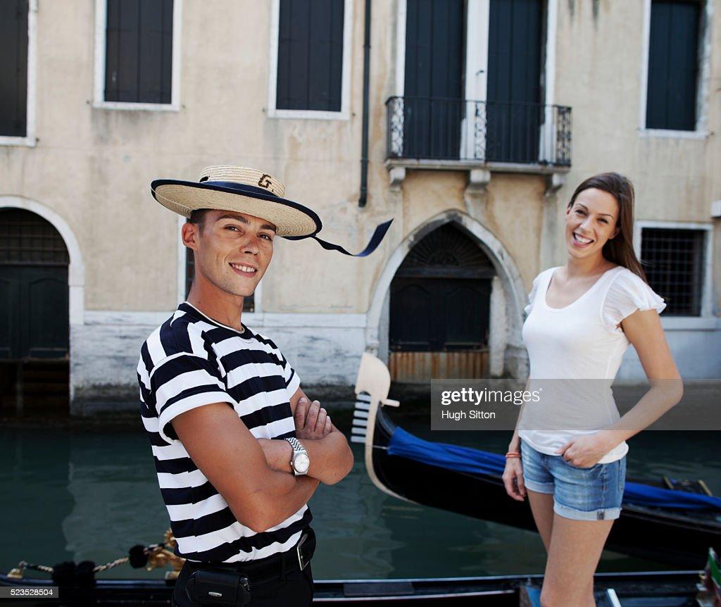 Portrait of smiling gondola driver and female tourist : Stock Photo