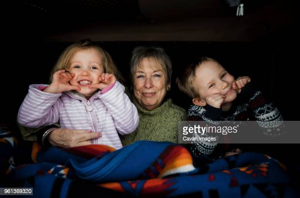 Portrait of smiling grandchildren with grandmother sitting in roof tent on car