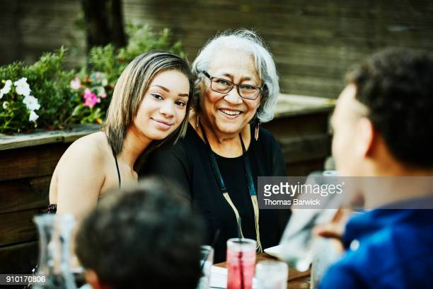 Portrait of smiling grandmother and granddaughter at outdoor family dinner party