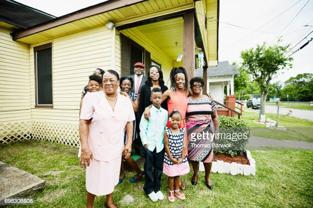 Portrait of smiling grandmother standing with family in front of house before going to church