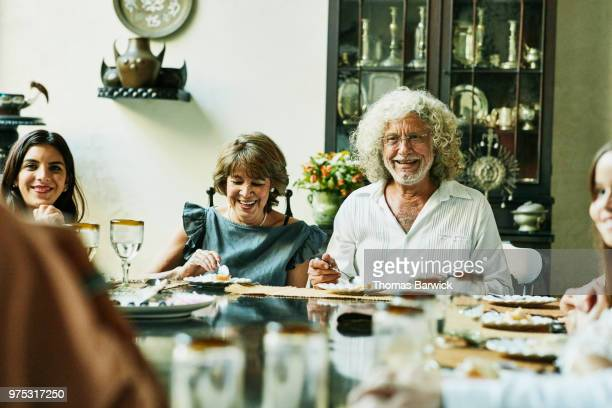 Portrait of smiling grandparents sitting at dining room table and eating cake during family birthday dinner