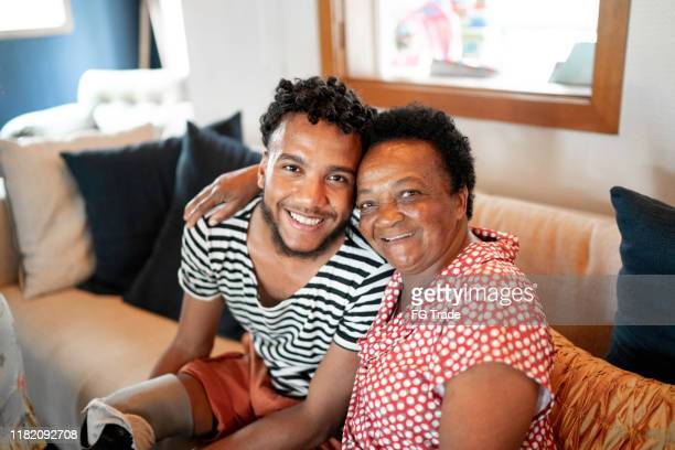 portrait of smiling grandson and grandmother - 18 19 years stock pictures, royalty-free photos & images