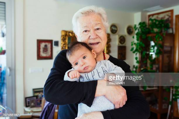 Portrait of smiling great-grandmother holding baby