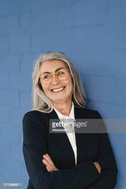 portrait of smiling grey-haired businesswoman standing at a blue wall - blazer azul - fotografias e filmes do acervo