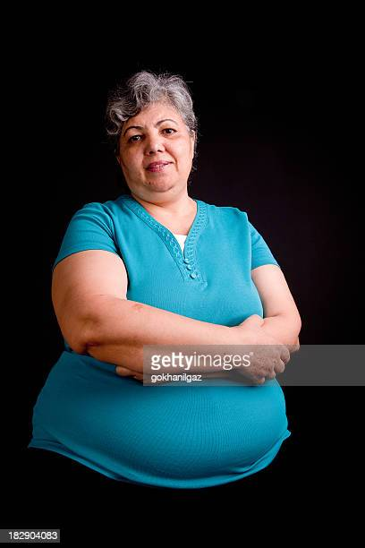 portrait of smiling grey-haired woman in black background - images of fat black women stock photos and pictures