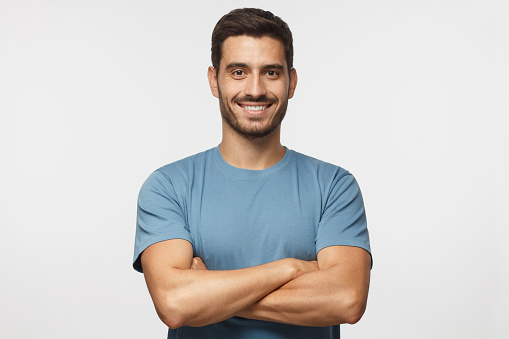 Portrait of smiling handsome man in blue t-shirt standing with crossed arms isolated on grey background 1045886560