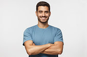 Portrait of smiling handsome man in blue t-shirt standing with crossed arms isolated on grey background