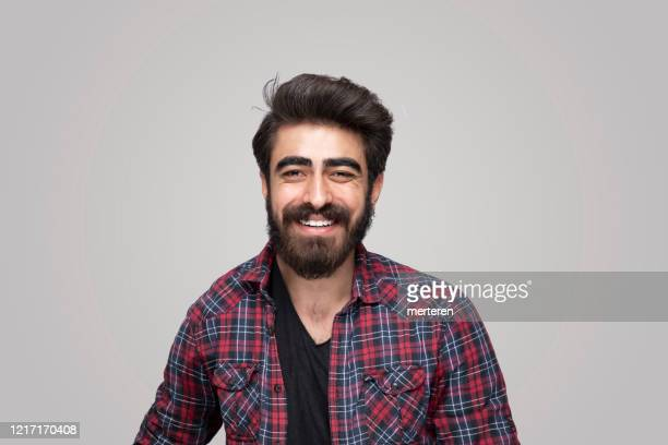 portrait of smiling handsome man looking at camera over isolated gray background - turkey middle east stock pictures, royalty-free photos & images