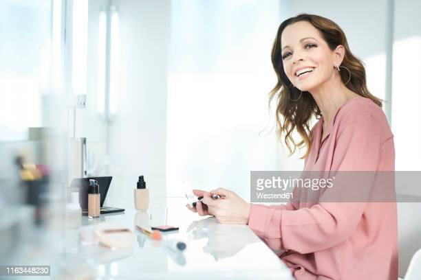 portrait of smiling happy applying make up at home - pink blouse stock pictures, royalty-free photos & images
