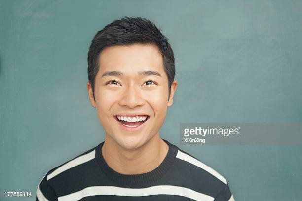 portrait of smiling, happy young man in front of blackboard - mouth open stock pictures, royalty-free photos & images