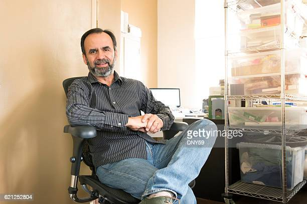 Portrait Of Smiling Hispanic Businessman Sitting In Desk Chair