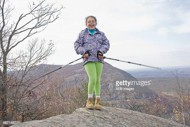 Portrait of smiling Hispanic girl on rock with hiking poles