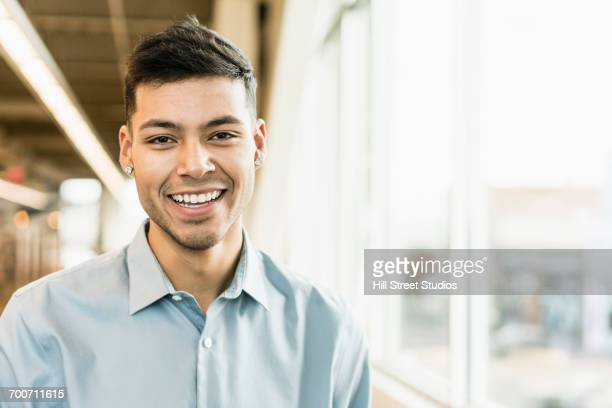 Portrait of smiling Hispanic man near window