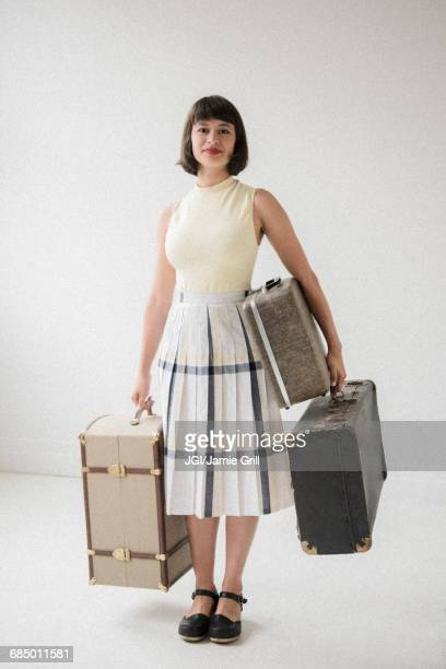 Portrait of smiling Hispanic woman holding suitcases