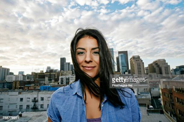 Portrait of smiling Hispanic woman on urban rooftop