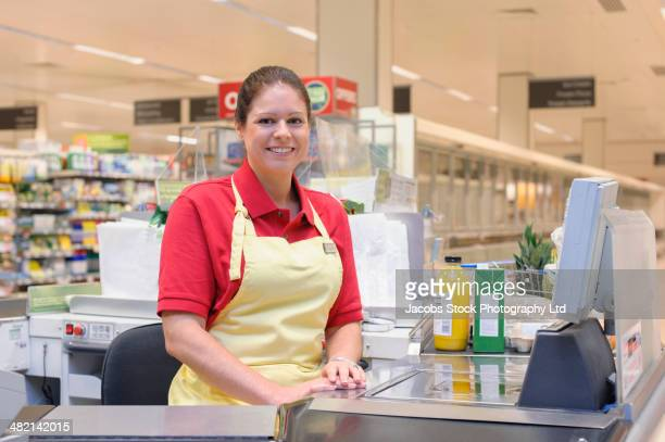 portrait of smiling hispanic woman working at grocery checkout - cashier stock pictures, royalty-free photos & images
