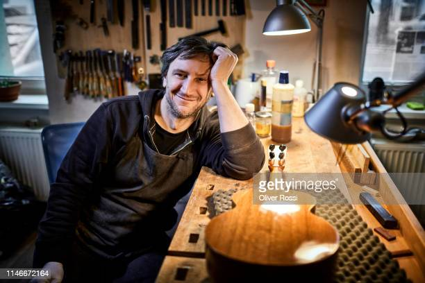 portrait of smiling instrument maker sitting in his workshop - ukulele stock pictures, royalty-free photos & images