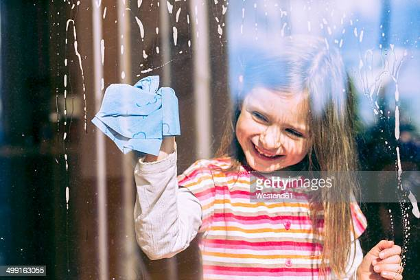 Portrait of smiling ittle girl cleaning window