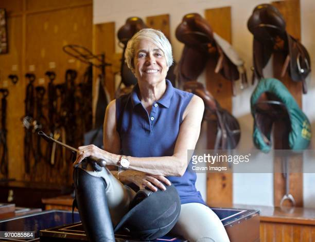 portrait of smiling jockey sitting on table in stable - riding crop stock photos and pictures