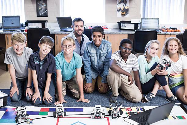 Portrait of smiling kids with teacher in robotics class