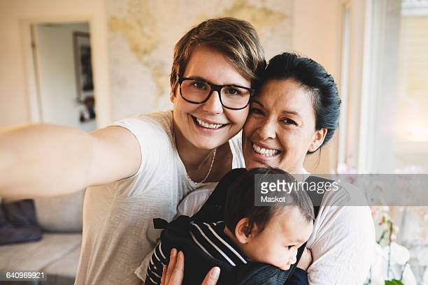 portrait of smiling lesbian couple with baby girl standing at home - twee ouders stockfoto's en -beelden
